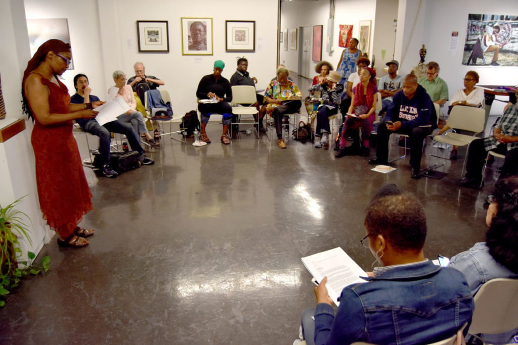 African American Master Artists In Residence Program director Gloretta Baynes speaks to program artists and supporters in the fourth-floor gallery at the studios at 76 Atherton St., Boston, Aug. 12, 2018. (Greg Cook)