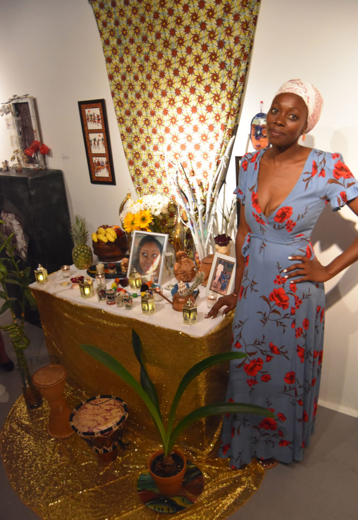 "Minu DaCosta with her shrine to her late sister: ""Earthbreed--Up Close & Personal,"" Dorchester Art Project, Boston, July 21, 2018. (Greg Cook)"