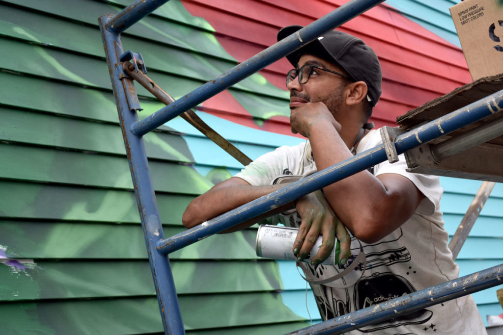 Angurria paints his mural at 112 Broadway, Somerville, Aug. 27, 2018. (Greg Cook)