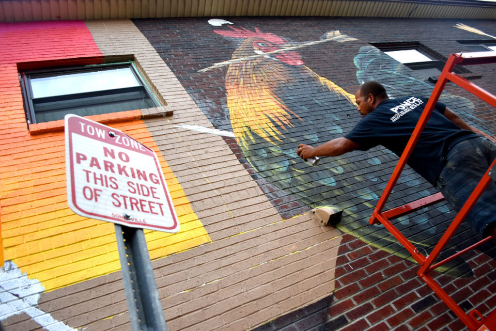 David Zayas paints his mural at 44 Broadway, Somerville, Aug. 27, 2018. (Greg Cook)