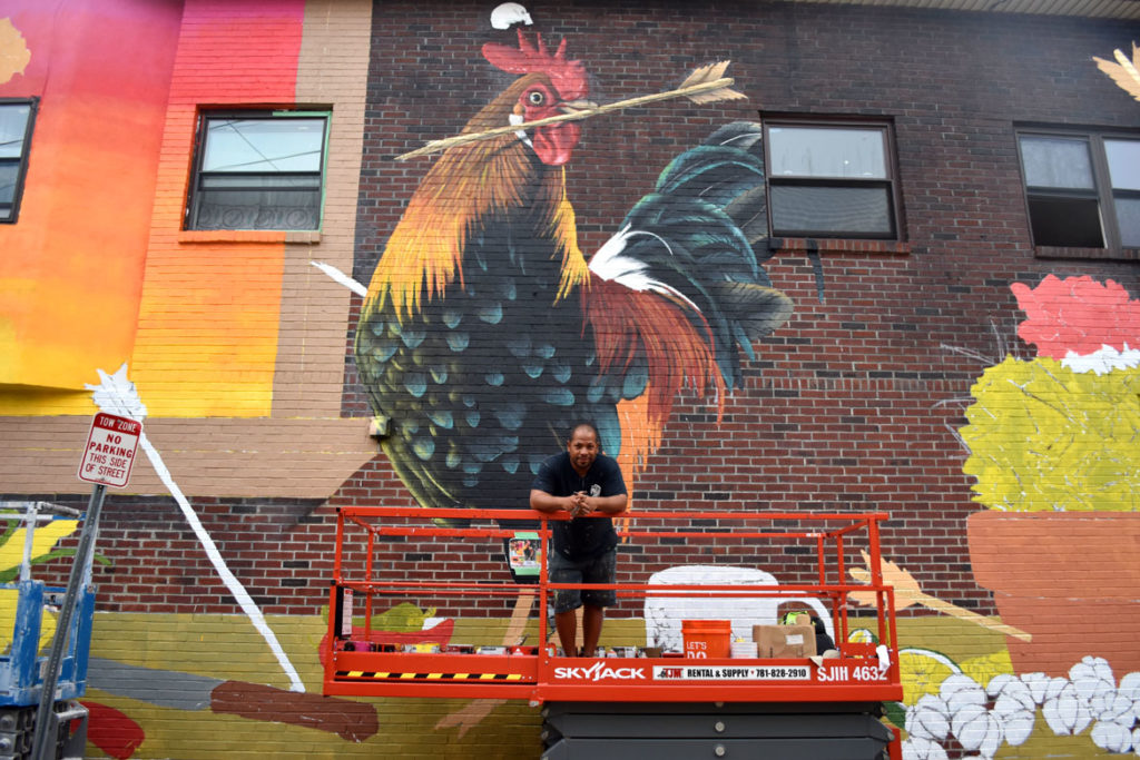 David Zayas with his mural at 44 Broadway, Somerville, Aug. 27, 2018. (Greg Cook)