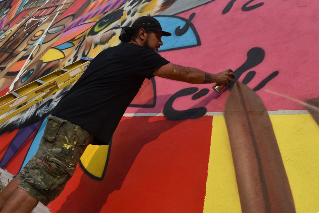 "Victor ""Marka27"" Quiñonez paints his mural ""Rebirth"" at 2 Union Square, Somerville, Aug. 27, 2018. (Greg Cook)"