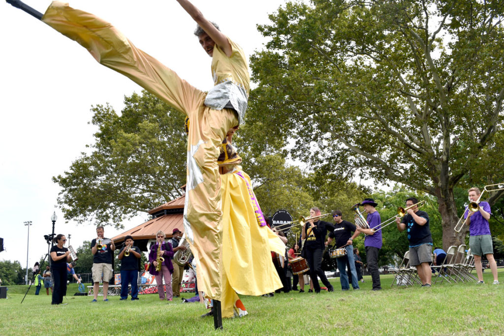 Stilter dances in front of Babam (Boston Area Brigade of Activist Musicians) at the Boston Rise for Climate, Jobs, Immigrant Rights & Justice rally at East Boston Memorial Park, Sept. 8, 2018. (Greg Cook)