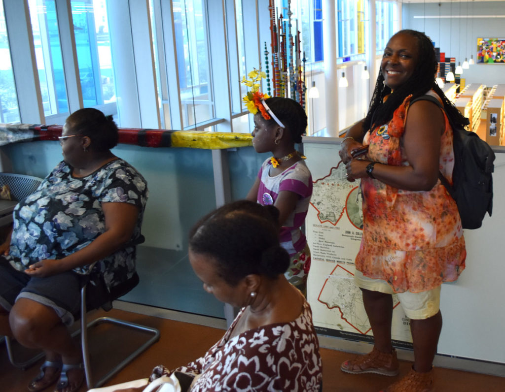 "Ekua Holmes (right) during her ""Celebrate the Sun"" party for her ""Roxbury Sunflower Project"" at the Grove Hall Branch of the Boston Public Library, Aug. 30, 2018. (Greg Cook)"
