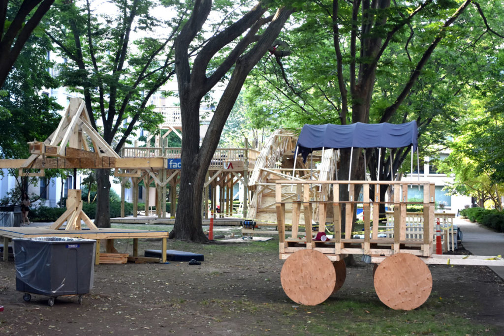 The wagon, swings and fort in the courtyard of Massachusetts Institute of Technology's East Campus residence hall, Cambridge, Aug. 28, 2018. (Greg Cook)