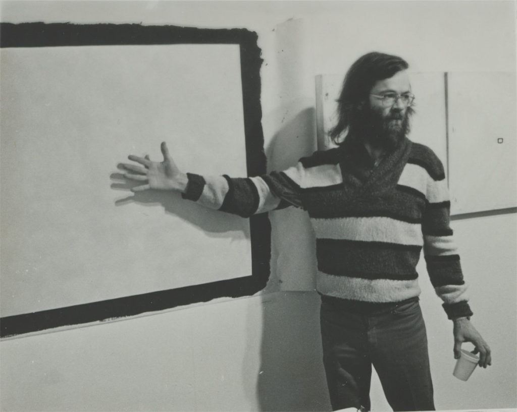 "Tony Conrad in front of ""Yellow Movie 2/2/73""(1973) and two ""YellowMovie—35mm Format canvases"" (1973), in his retrospective exhibition, Hallwalls Contemporary Arts Center, Buffalo, New York, December 1977. (Photo: Kevin Noble)"
