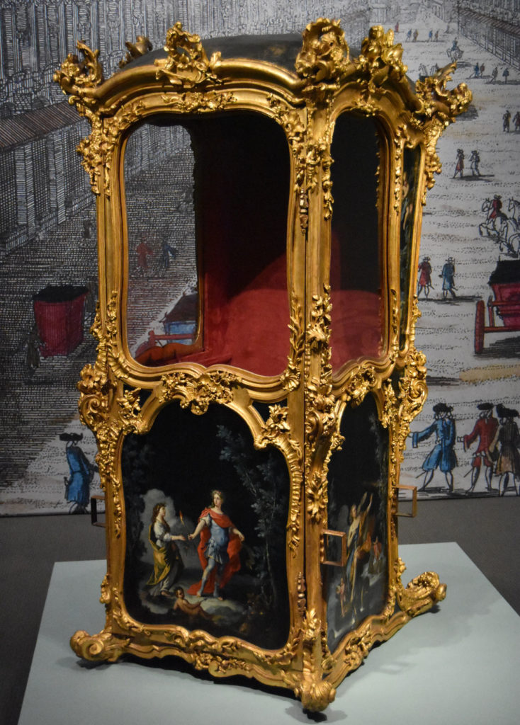 Sedan chair, Italy (probably Naples), possibly mid-18th century, gilded wood frame with painted panels, glass, gilded metal fittings, and silk upholstery. (Greg Cook)