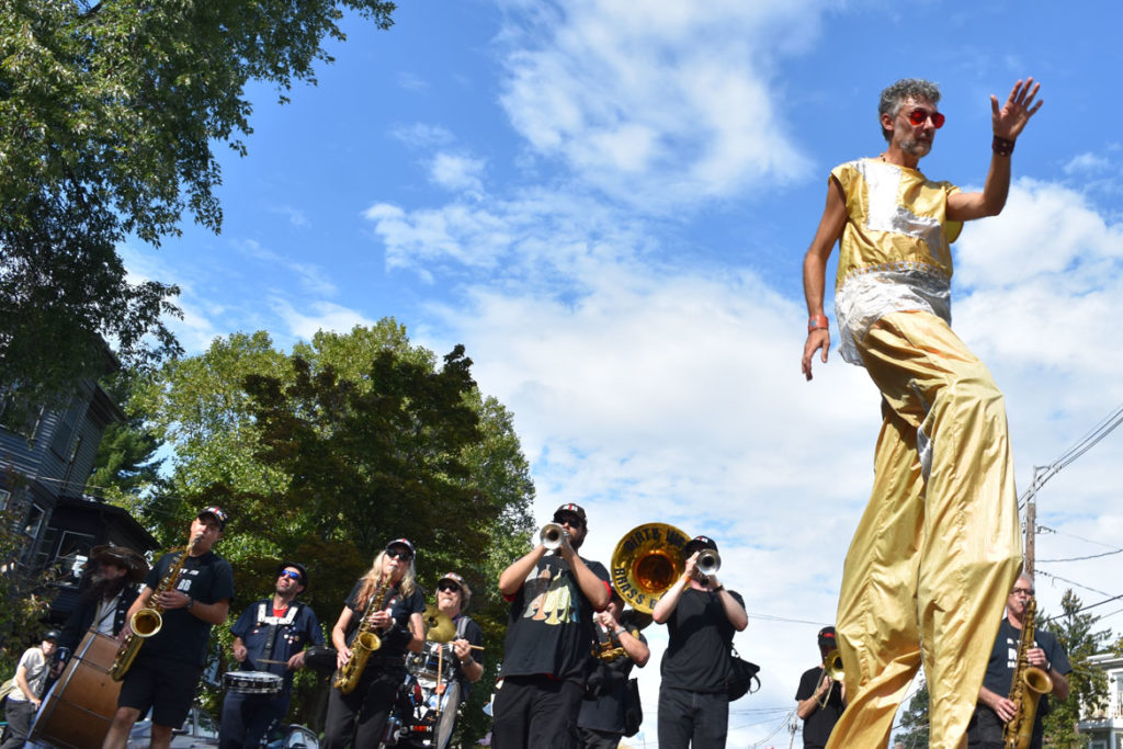 Shawn Morrissey stilts with the Dirty Water Brass Band from Boston in the Honk Parade, Oct. 7, 2018. (Greg Cook)