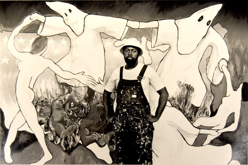 "Dana Chandler stands in front of his painting ""Sakkkraficial Dance"" in a photo promoting its inclusion in the Museum of Fine Arts' 1984 exhibition ""Emerging Massachusetts Painters."""