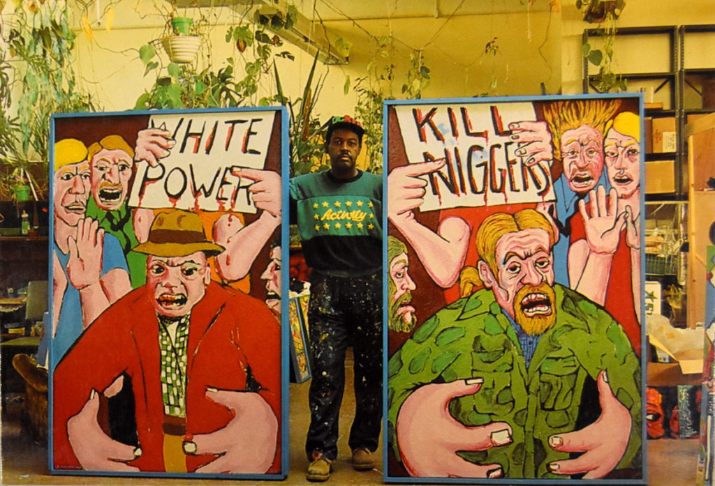 "Dana Chandler photographed in his studio for the postcard for his ""The more things change, the more things remain the same, Let My People Go!"" retrospective at Massachusetts College of Art, Feb. 23 to March 20, 1987. On the left is his painting ""The Beast,"" 1967-68, and on the right is ""The Beast Revisited-Forsyth County, Georgia,"" 1987."