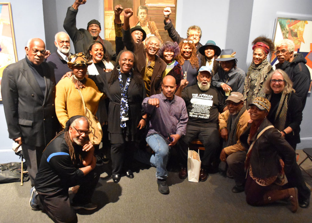 Members of the African American Master Artists In Residence Program and friends gather at a celebration of founder Dana Chandler (seated in black shirt) at the Museum of the National Center of Afro-American Artists in Roxbury, Nov. 3, 2018. (Greg Cook)