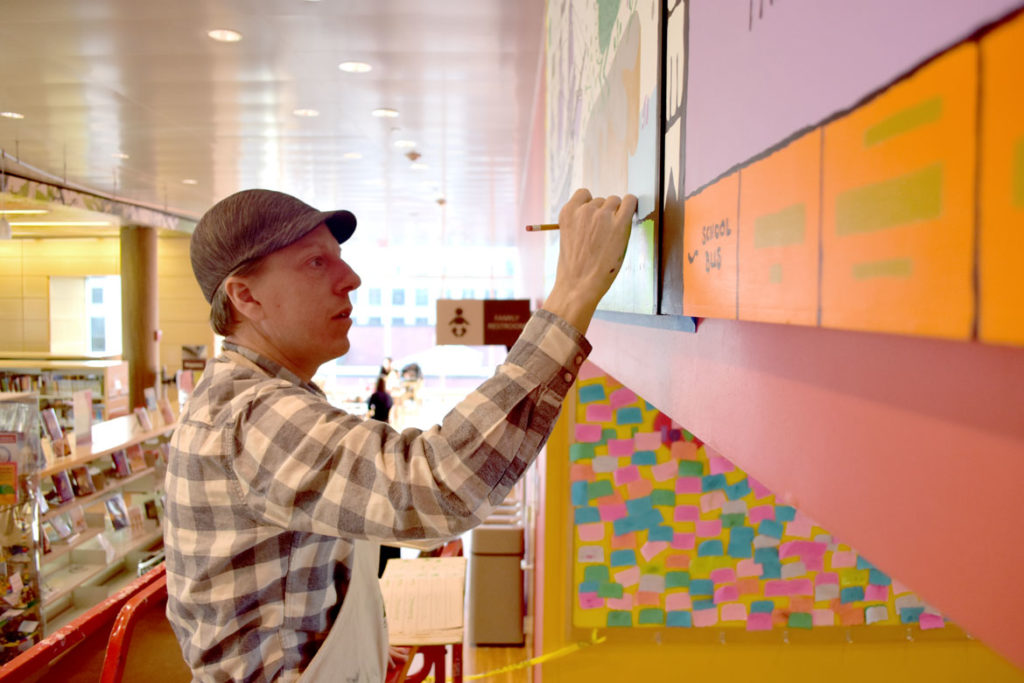 "Caleb Neelon pains his Ed Emberley ""Drawing Books"" mural at the Cambridge Public Library's Children's Room, Jan. 17, 2019. (Greg Cook)"