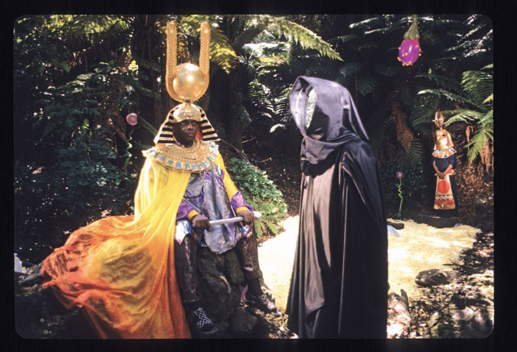 """Space is the Place Film Still,"" 1974, by Jim Newman. ""Sun Ra and his mysterious mirror-faced companion in Golden Gate Park. The photo is from the opening sequence of the film in which Sun Ra wanders a lush unspecified planet and outlines his theory on how we can move through space propelled by music, a theoretical way of travel he calls 'trans-molecularization.'"" (Courtesy Portland Art Museum)"