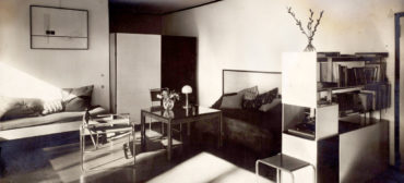 """At Harvard Art Museums: Lucia Moholy, """"Bauhaus Masters Housing, Dessau (Lucia Moholy and László Moholy-Nagy's living room),"""" 1927–28. Gelatin silver print with opaque watercolor retouching. (Harvard Art Museums/Busch-Reisinger Museum)"""