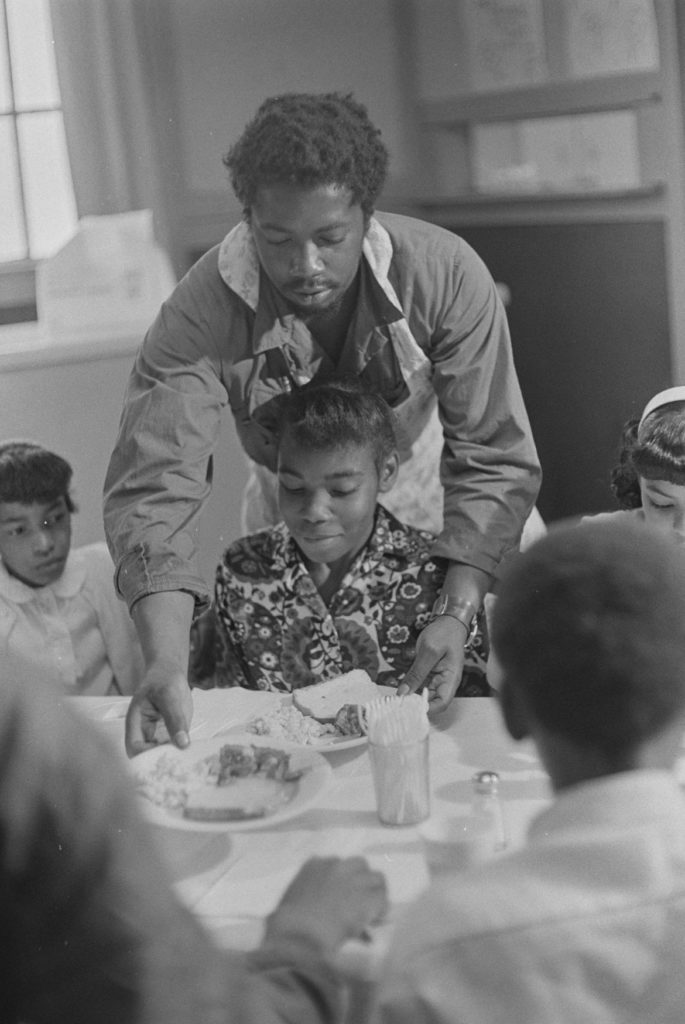 "Ruth-Marion Baruch, ""Charles Bursey serving children at Black Panther Free Breakfast for Children Program, St. Augustine's Episcopal Church,"" May 19, 1969. (Courtesy University of California, Santa Cruz)"