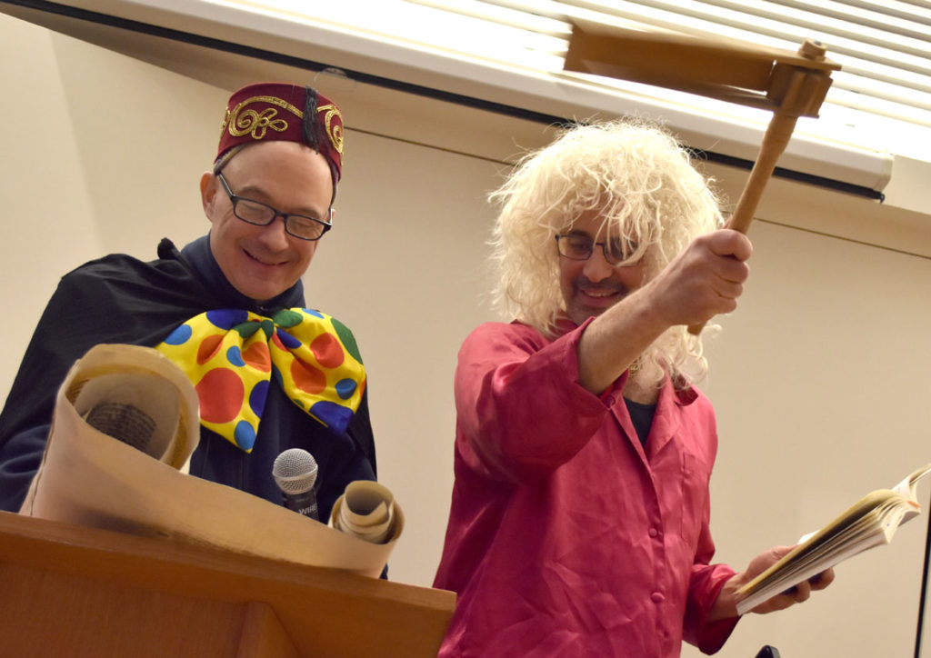 Rabbi Steven Lewis (right) shakes the granger during the reading of the megillah at the Purim Party at Gloucester's Temple Ahavat Achim, March 20, 2019. (Greg Cook)