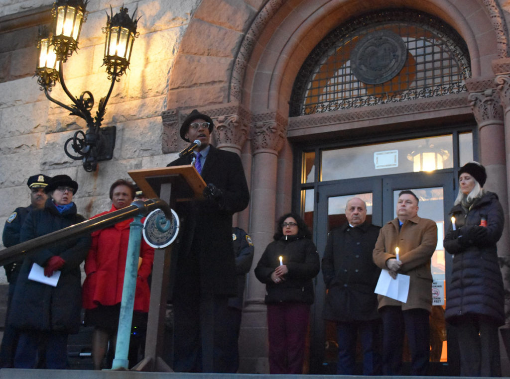 "Brian Corr of the Cambridge Peace Commission speaks at the ""Candlelight Vigil for Victims of the New Zealand Mosque Attacks."" at Cambridge City Hall, March 19, 2019. (Greg Cook)"