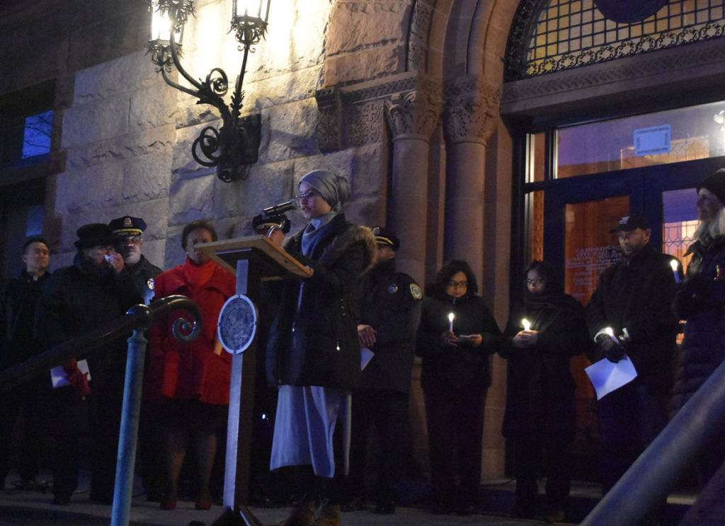 "Farida Mustafa speaks at the ""Candlelight Vigil for Victims of the New Zealand Mosque Attacks."" at Cambridge City Hall, March 19, 2019. (Greg Cook)"
