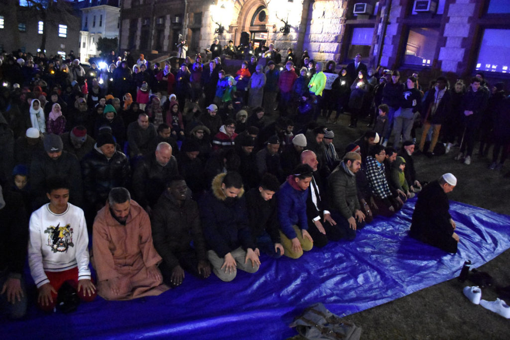 "Maghrib (evening) prayer during the ""Candlelight Vigil for Victims of the New Zealand Mosque Attacks."" at Cambridge City Hall, March 19, 2019. (Greg Cook)"