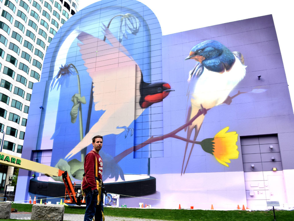 "Super A (Stefan Thelen) with his mural (in progress) ""Resonance"" on Boston's Greenway in Dewey Square, April 29, 2019. (Greg Cook)"