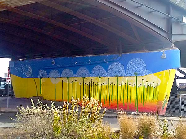 Nate Swain's guerrilla mural of sunflowers on supports under Route 93 in Sullivan Square, Boston. (Courtesy)