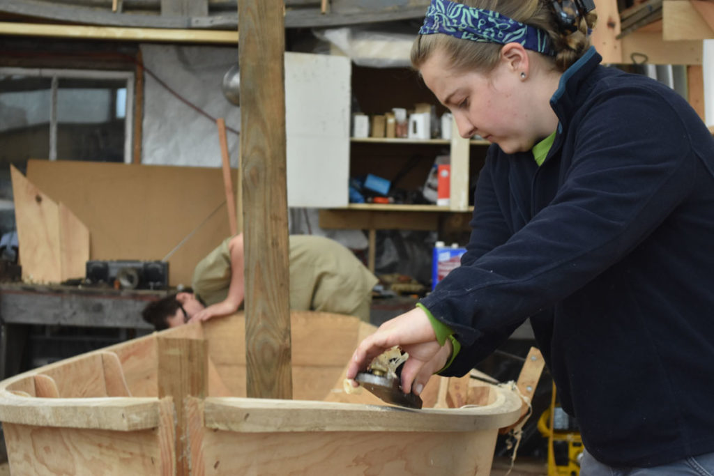 Susannah Winder, Education and Group Program Coordinator, planes an Essex clamming skiff at the Essex Historical Society and Shipbuilding Museum in Essex, April 26, 2018. (Greg Cook)