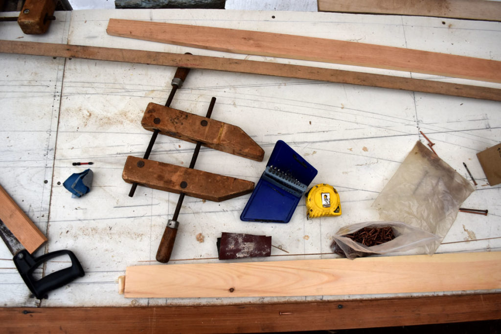 Tools lay atop measurements of the lines from a century old Essex clamming skiff at the Essex Historical Society and Shipbuilding Museum in Essex, April 26, 2018. (Greg Cook)