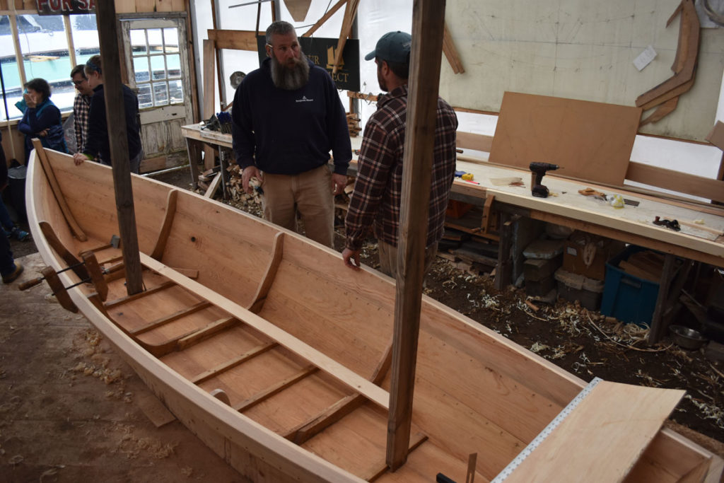 Mark Webster of Topsfield Vocational Academy (left) and Jeff Lane, an Essex Shipbuilding Museum boat builder and instructor, work on an Essex clamming skiff at the Essex Historical Society and Shipbuilding Museum in Essex, April 26, 2018. (Greg Cook)