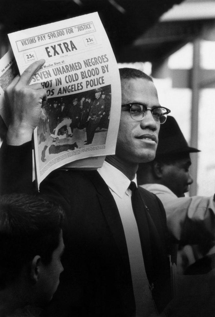 "Gordon Parks ""Malcolm X Holding Up Black Muslim Newspaper, Chicago, Illinois,"" 1963 Gelatin Silver Print. (Courtesy of the Gordon Parks Foundation)"
