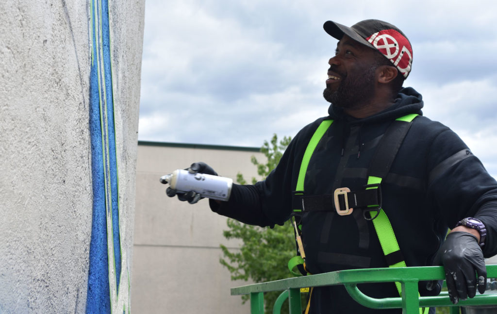 "Rob ""ProBlak"" Gibbs paints his ""Breathe Life 3"" mural at 808 Tremont St., Boston, May 24, 2019. (Greg Cook)"