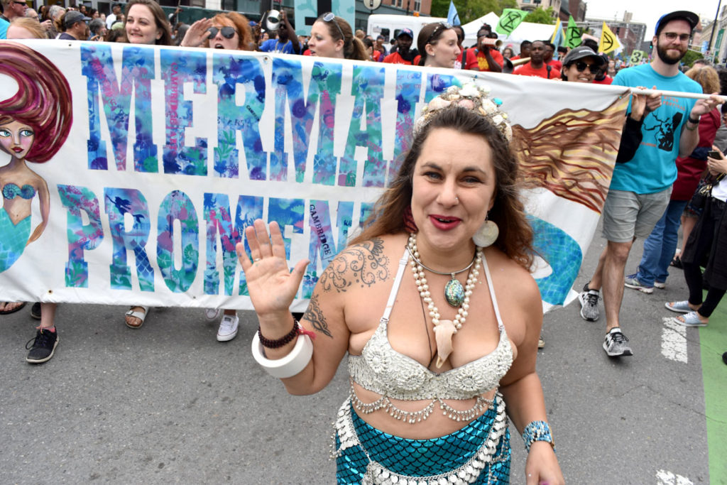 Julz Roth with the banner she made leads the Mermaid Promenade at Cambridge Arts River Festival in Central Square, June 1, 2019. (Greg Cook)