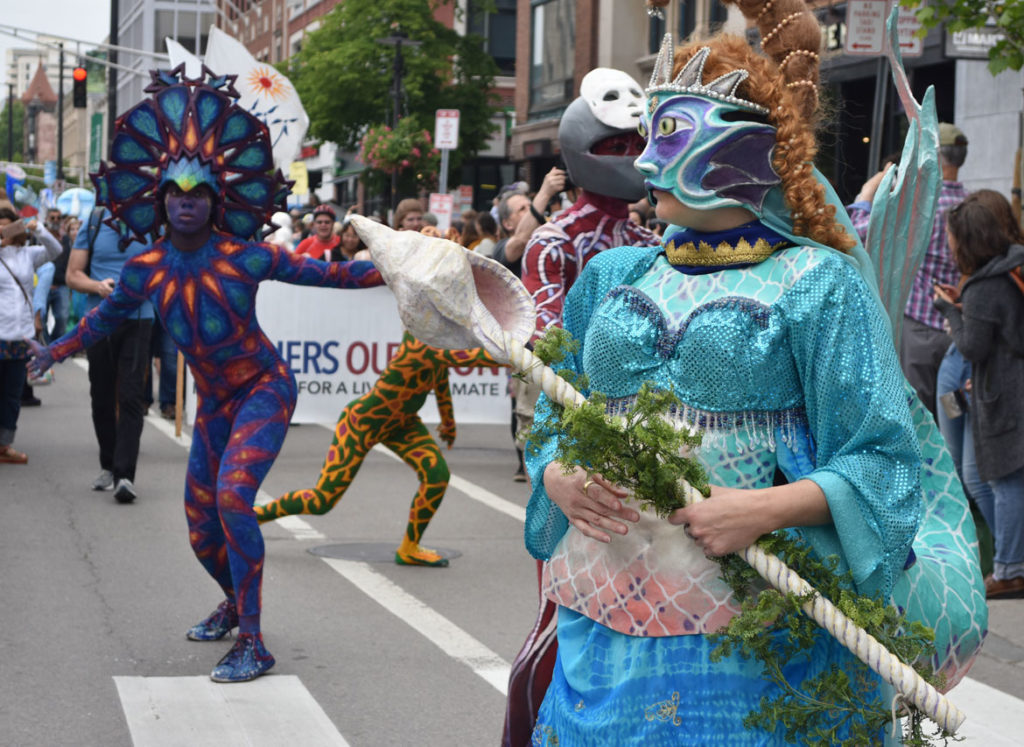 Behind the Mask Studio mermaid followed by Fine Art Superheroes in the Mermaid Promenade at Cambridge Arts River Festival in Central Square, June 1, 2019. (Greg Cook)
