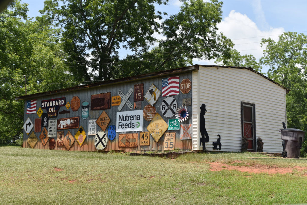 Building covered with signs at 1116 Georgia Rt. 27, Americus, Georgia, June 23, 2019. (Greg Cook)