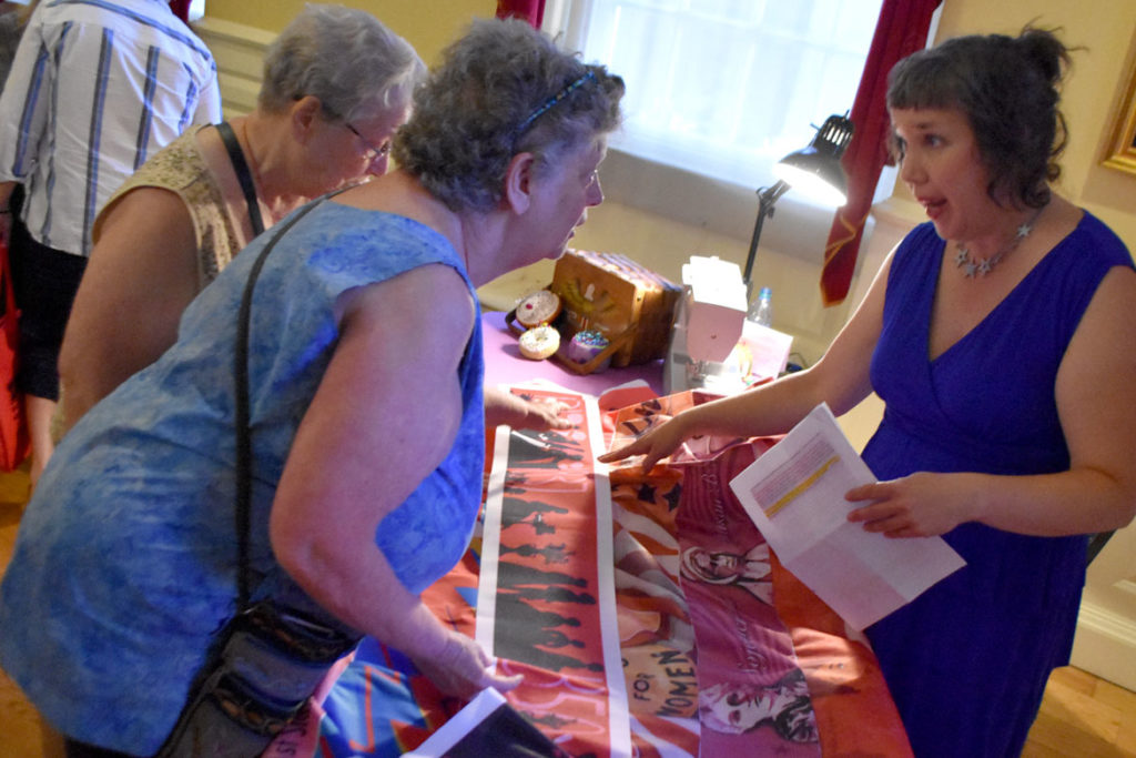 """Kari Percival (right) speaks about the stripe she illustrated for """"Her Flag"""" at the Old State House, Boston, July 25, 2019. (Greg Cook)"""