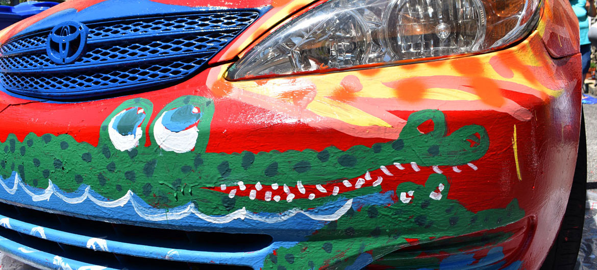 Painting Mark Alston-Follansbee's Toyota Camry art car in the driveway of his Waltham home, July 7, 2019. (Greg Cook)