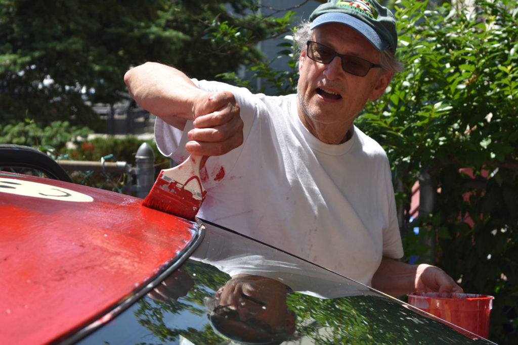 Mark Alston-Follansbee paints his Toyota Camry art car in the driveway of his Waltham home, July 7, 2019. (Greg Cook)