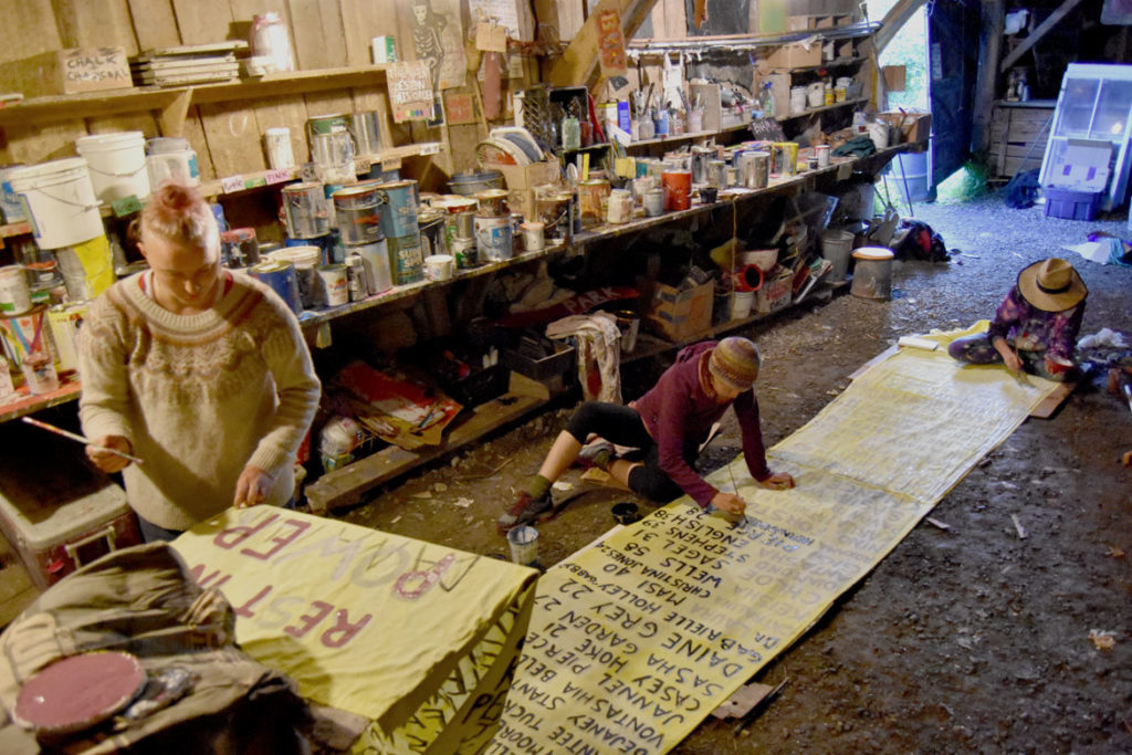 "Painting banner ""In Honor of Trans Lives Cut Short"" for Bread and Puppet Theater's ""Diagonal Life Circus,"" under the museum barn, Glover, Vermont, Aug. 24, 2019. (Greg Cook)"