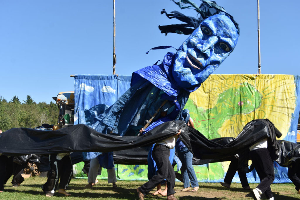 "A black pipeline threatens blue water in Bread and Puppet Theater's ""Diagonal Life Circus,"" Glover, Vermont, Aug. 25, 2019. (Greg Cook)"