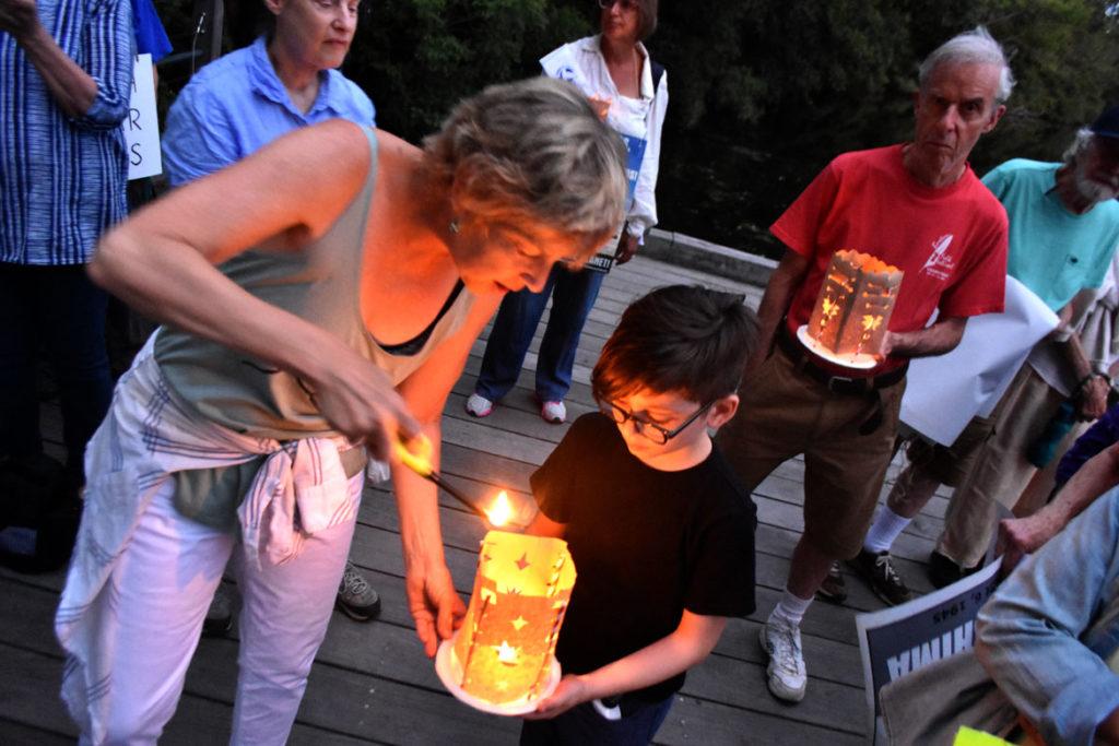 Lighting the lanterns during the Remembering Hiroshima and Nagasaki Vigil in Watertown Square, Aug. 4, 2019. (Greg Cook)