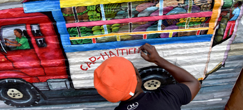 Pascal Michel paints his mural on the side of Highland Creole Cuisine, 2 Highland Ave., Somerville, Aug. 28, 2019. (Greg Cook)