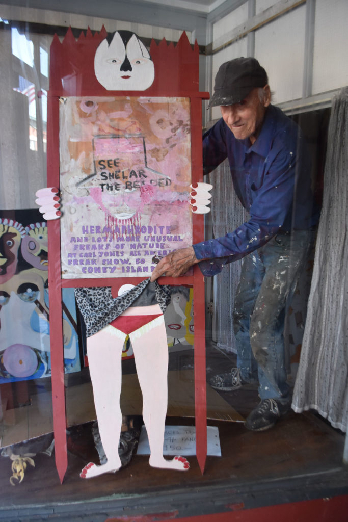 "Stephen Leakos with his ""Hermaphrodite"" painting in the window of his Skowhegan Downtown Art Gallery, Skowhegan, Maine, Jul 30, 2019. (Greg Cook)"