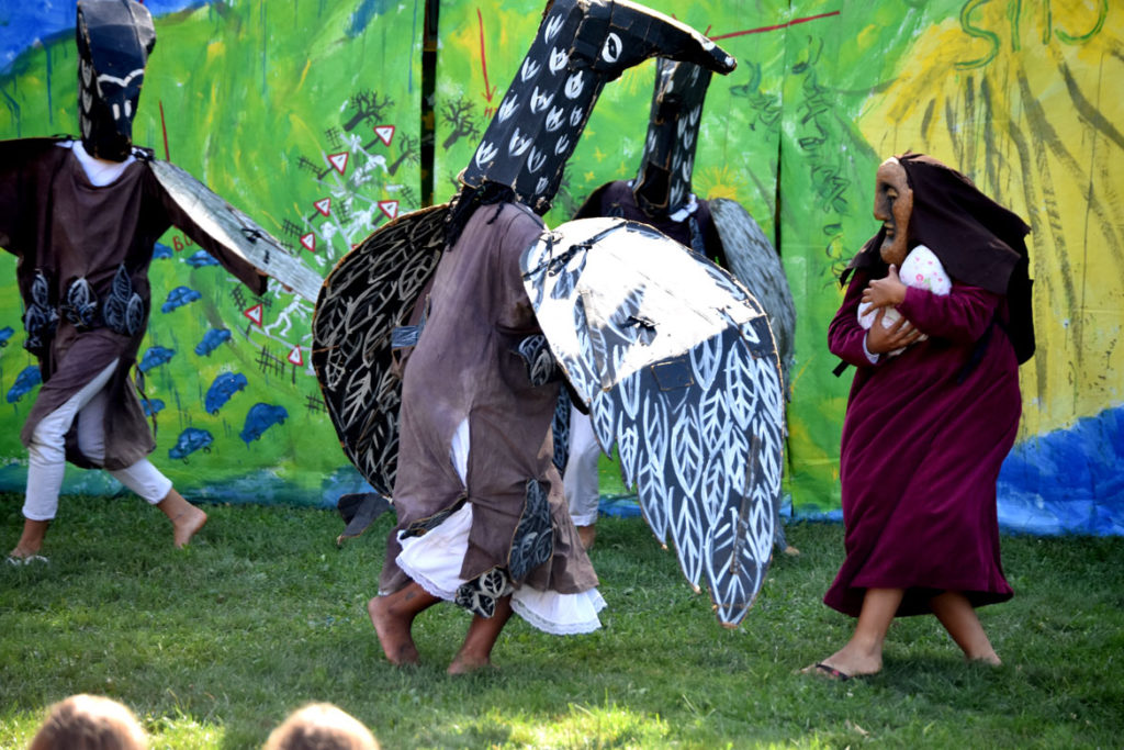 "A migrant mother is threatened by birds during Bread and Puppet Theater's ""Diagonal Life Circus"" at Cambridge Common, Aug. 31, 2019. (Greg Cook)"