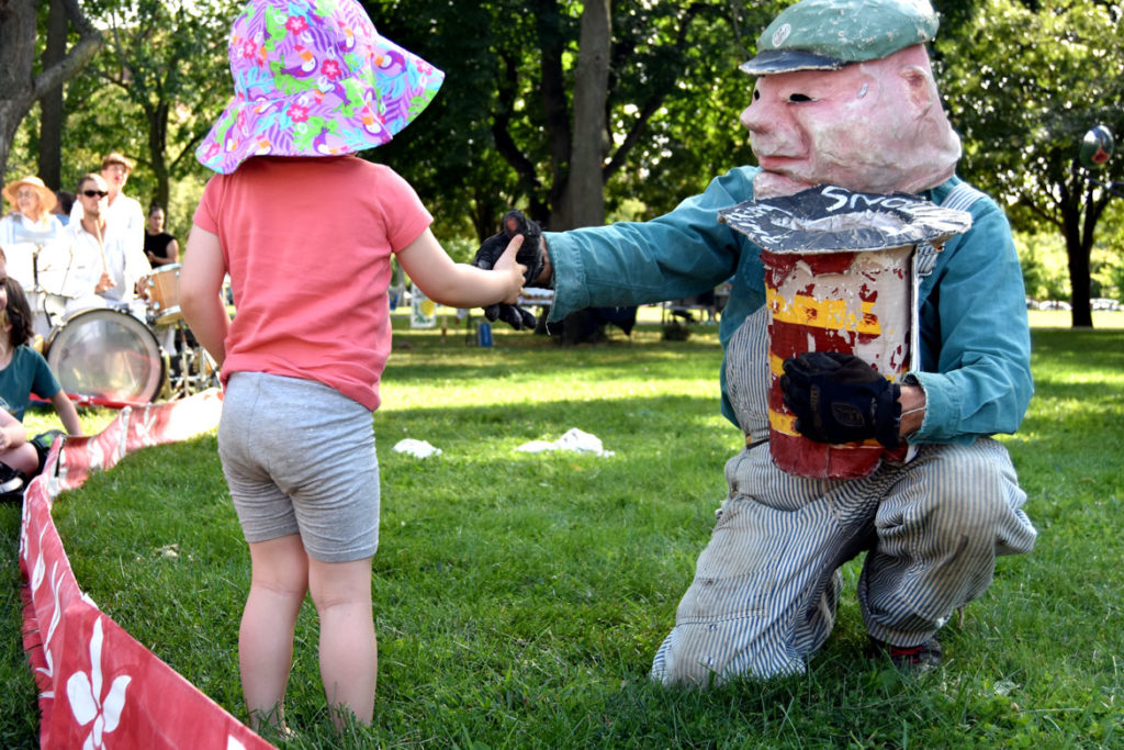 "A garbage man greets an audience member before Bread and Puppet Theater's ""Diagonal Life Circus"" at Cambridge Common, Aug. 31, 2019. (Greg Cook)"
