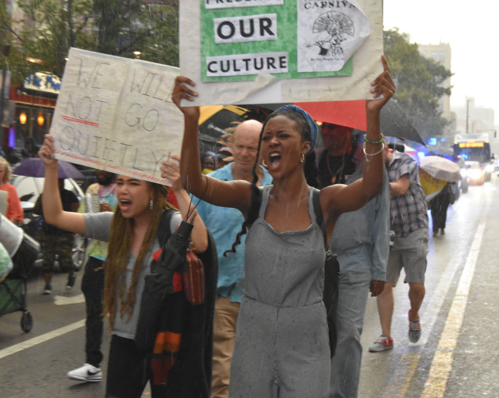 """""""We will not go quietly."""" """"Preserve our culture."""" Signs at the """"March for Peace"""" down Cambridge's Massachusetts Avenue in response to the cancellation of the 2019 Carnival. Sept. 4, 2019. (Greg Cook)"""