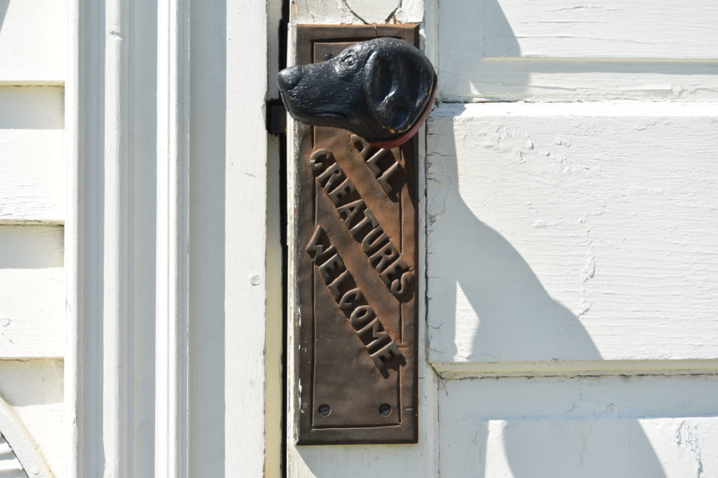 """All Creatures Welcome"" doorknob on the front of Stephen Huneck's Dog Chapel, St. Johnsbury, Vermont, Aug. 26, 2019. (Greg Cook)"