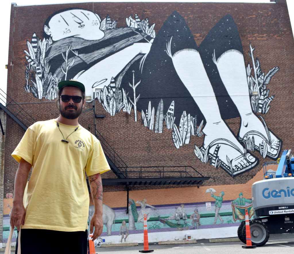 Alex Senna with his mural on the Cabot Theatre, Beverly, Massachusetts, July 20, 2019. (Greg Cook)
