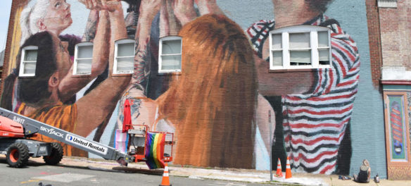 Helen Bur finishes painting her mural on the Cabot Theatre, Beverly, Massachusetts, July 20, 2019. (Greg Cook)
