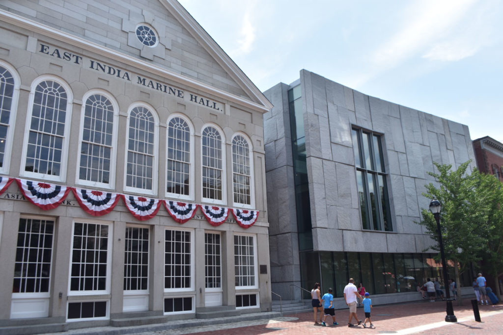 The Peabody Essex Museum's new wing (at right) designed by the New York firm Ennead Architects sits beside the East India Marine Hall on Salem's Essex Street, July 20, 2019. (Greg Cook photo)