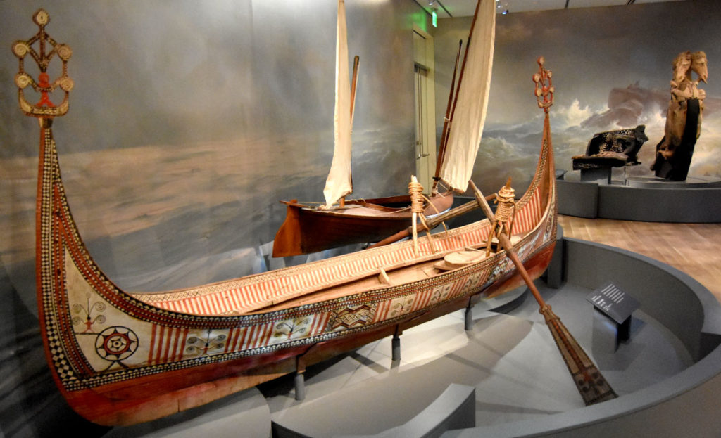 """Tatara canoe by Yami people of Orchard Island, Taiwan, from about 1974, and sailing canoe """"Urchin"""" 1884 designed by George Underwood while he was a student at Massachusetts Institute of Technology. In the maritime galleries of the Peabody Essex Museum's new wing, Salem, Sept. 25, 2019. (Greg Cook photo)"""