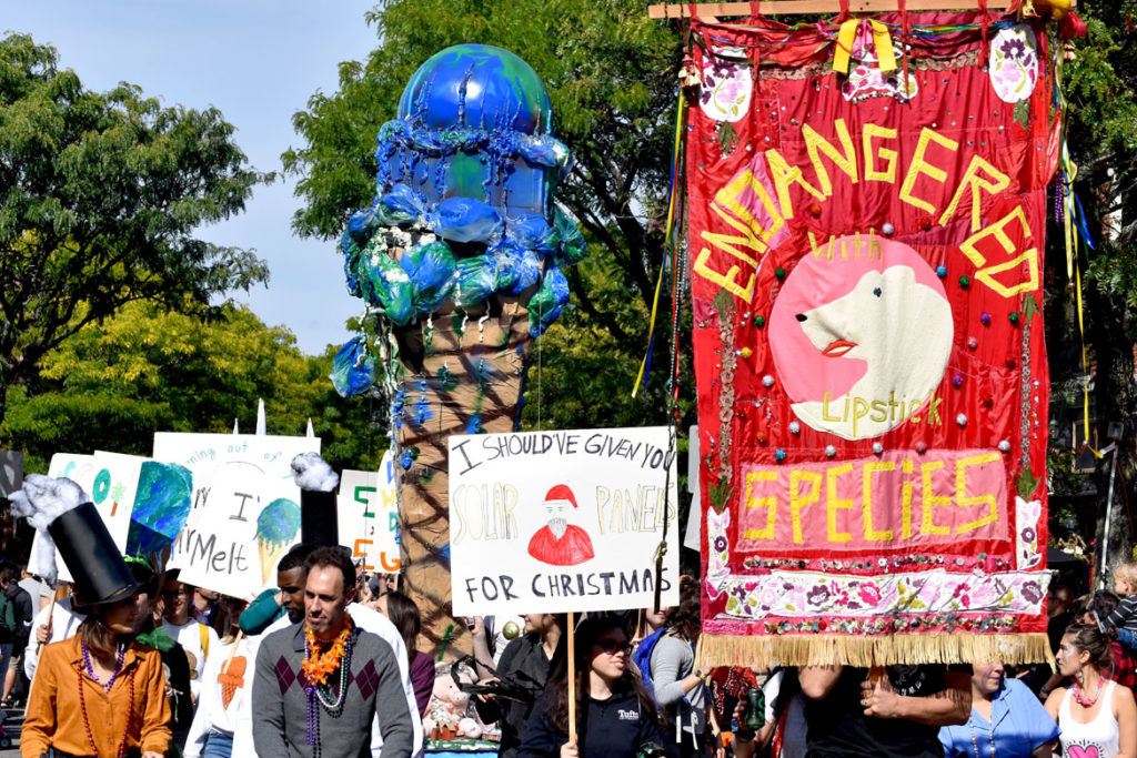 Global warming activists from Tufts University march through Somerville's Davis Square during the Honk Parade, Oct. 13, 2019. (Greg Cook photo)